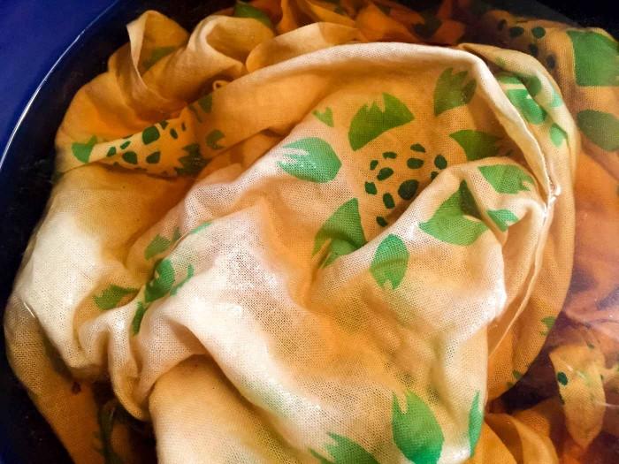 玉葱の皮からできた染料液に布を浸す